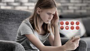 Ein Bild von einem Mädchen das auf ein Smartphone starrt. Ihr Gesichtausdruck ist eher verzweifelt, neben Ihr sind auch traurige und böse Emojis abgebildet.